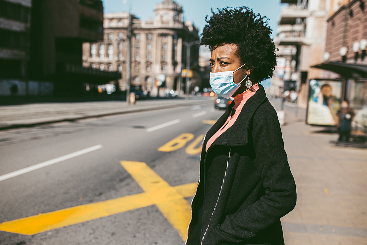 Young African American woman standing on city street with protective mask on her face.