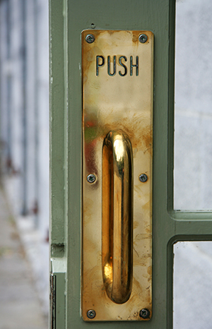 "A brass door handle with sign ""PUSH""."